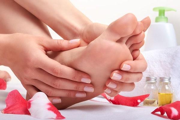 Ápolt kéz és láb, mellette kozmetikai termékek, illóolajok, puha törülközők.