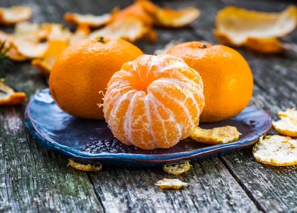 Három mandarin kistányéron, az egyikről lebontva a héja.