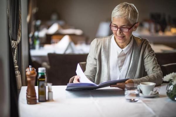 Idősebb hölgy olvassa az étlapot egy étteremben.