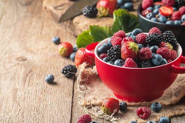 Bogyós gyümölcsök vegyesen egy óriás, piros bögrében.