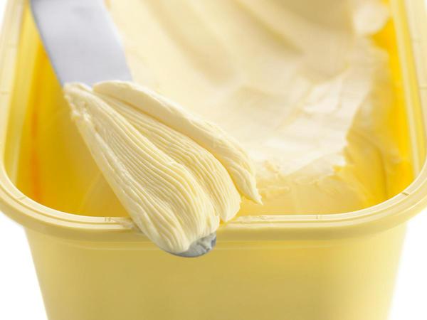 Dobozos margarinból késre kenve egy darabka.