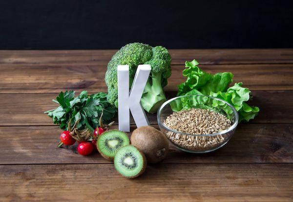 K-vitamint tartalmazó élelmiszerek, köztük egy fehér K betű.