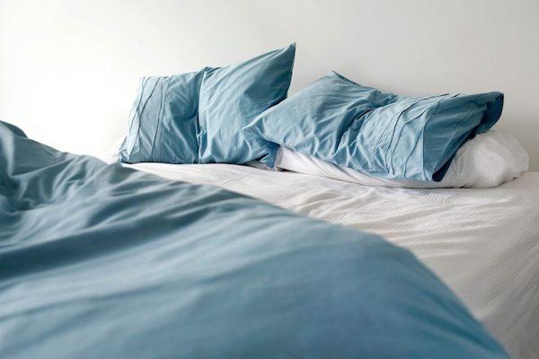 Fáradt kék színű ágynemű a bevetetlen ágyon.