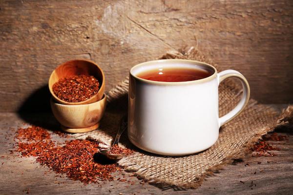 Afrikai vörös tea, más néven rooibostea pohárban, mellette a szálas tea külön tartóban.