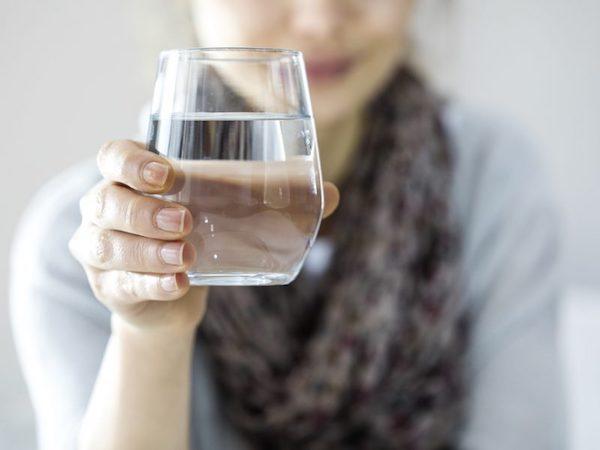 Egy pohár vizet tart kezében egy hölgy.