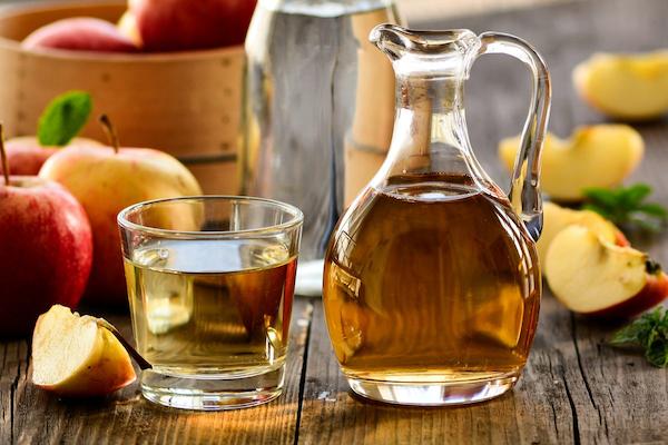 Almaecet kis kancsóban és pohárban, körülöttük sok-sok alma egészben és negyedelve.