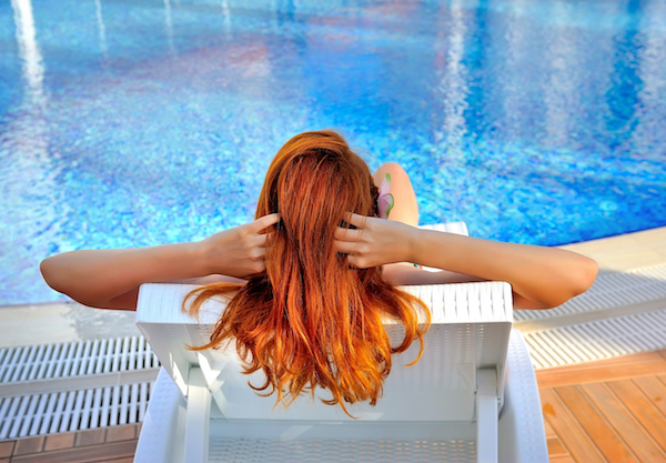 Vörös hajú nő haját igazgatja a medence partján.