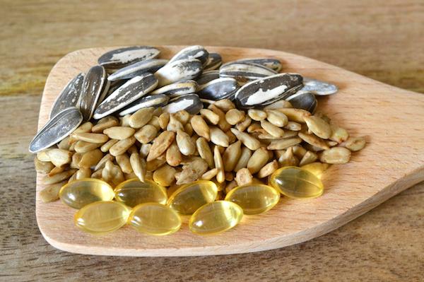 E-vitaminok és napraforgómagok egy nagy fakanálon.