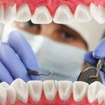 Műanyag fogsor makettet vizsgál egy lila gumikesztyűs fogorvos.
