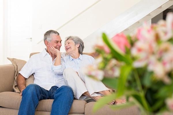 Idősebb házaspár együtt nevetgél a kanapén.