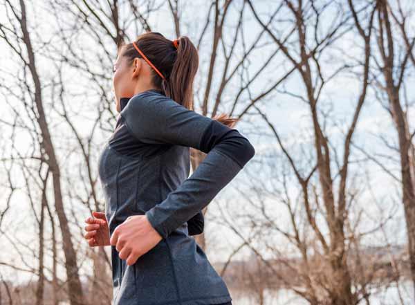 Fiatal nő futódzsekiben fut egy téli napon.