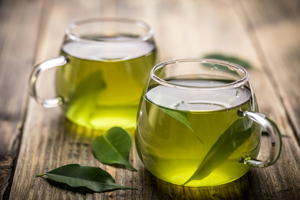 Két pohárban zöld tea az asztalon.