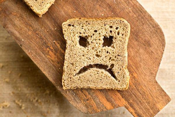 Lekonyuló szájú arc egy kenyérszeletre lyuggatva.