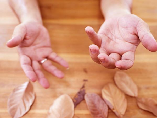 Parkinsonos hölgy keze egy őszi asztal fölött.