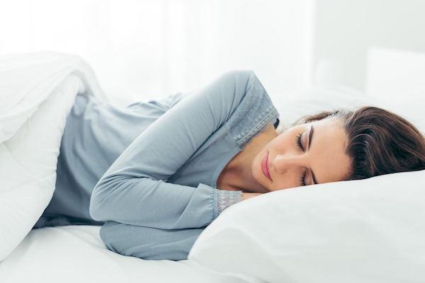 Fiatal nő alszik az ágyában.