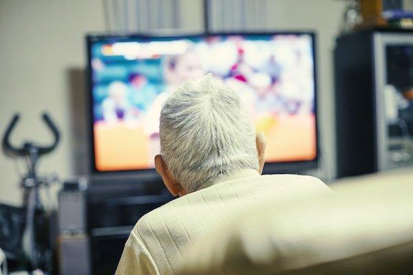 Idős bácsi ül a televízió előtt.