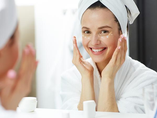 Fiatal lány szemránckrémet ütöget bőrébe mosolyogva a tükör előtt.