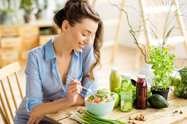 Fiatal, húszas éveiben járó hölgy salátát eszik, mellette friss fűszernövények, avokádó és smoothiek.