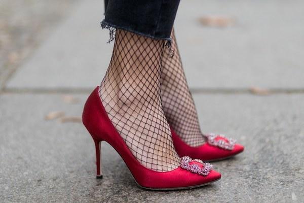Tűzpiros Manolo Blahnik cipő díszcsattal egy neccharisnyás női lábon.