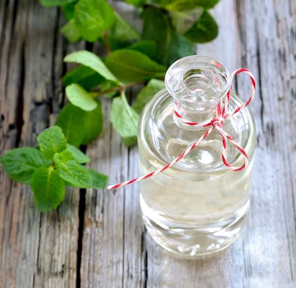 Borsmentaolaj átlátszó üvegben, melynek piros-fehér csíkos fonal van a nyakán.