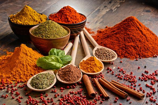 Különféle, színes indiai fűszerek egyfroma fakanalakban egymás mellett.
