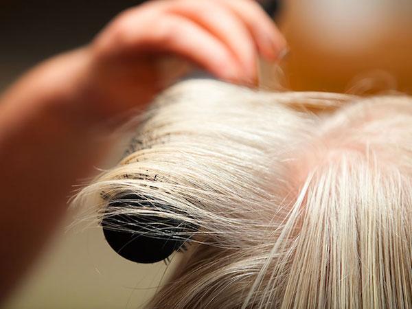 Vékony hajú szőke hölgy körkefével formázza a haját.