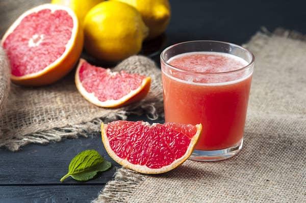 Grépfrút és a gyümölcsből kipréslet friss juice, a háttérben citromok.