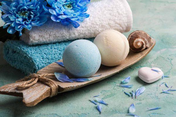 Kék és fehér színű fürdőbombák egy hal alakú fatálon.