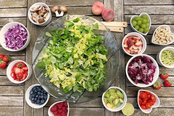 Sok flavonoidot tartalmazó zöldségek és gyümölcsök kisebb és nagyobb tálakban.