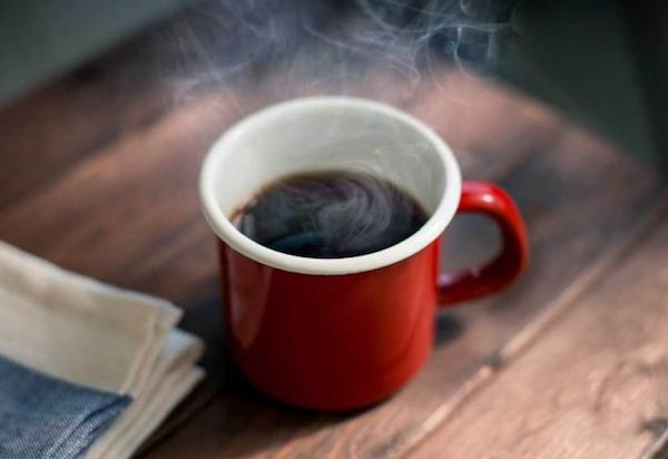 Egy piros, zománcozott bögrében gőzölög a fekete kávé.