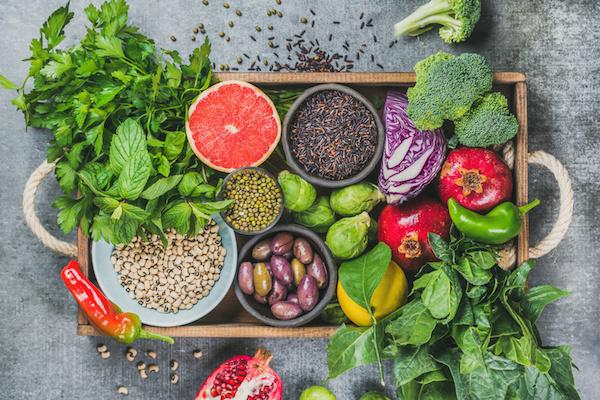 Anyagcserét gyorsító táplálékok egy tálcán: friss zöldségek, gyümölcsök és fűszernövények.