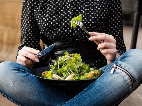 Törökülésben lévő hölgy salátát eszik.