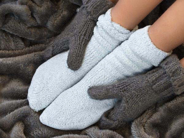 Vastag, meleg takarón ül egy zoknit, kesztyűt viselő hölgy.