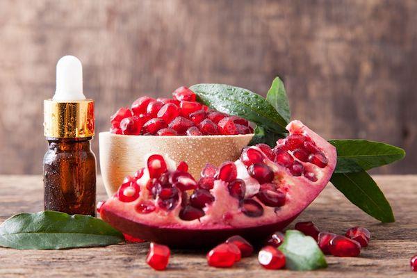 Gránátalmamagok, maga a gyümölcs és a belőle készült arcápoló olaj kis üvegben.