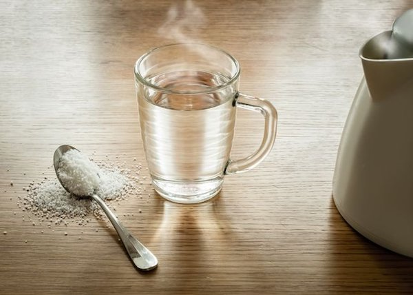 Egy bögre forró vz, mellette egy kiskanál só.