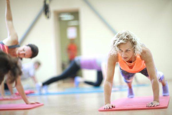 Idősebb hölgy csoportos edzésen vesz részt egy edzőteremben.