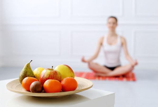 Jógázó hölgy, az előtérben gyümölcsöstál almával, körtével, mandarinnal és kivivel.