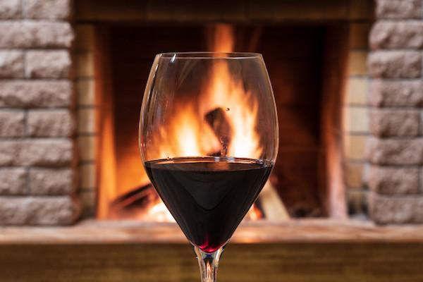 Egy pohár vörösbor a kandalló tüze előtt.