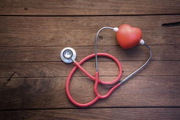 Faasztalon egy piros fonendoszkóp, amelyet egy műanyag szívhez csatlakoztatnak.