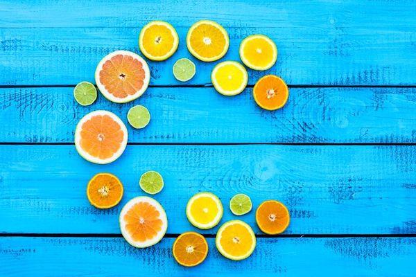 C betű alak kirakva citrusfélékből, karikára vágott narancsokból, citromokból és lime-okból.