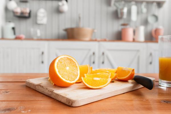 Narancs cikkekre vágva vágódeszkán egy konyha pultján.