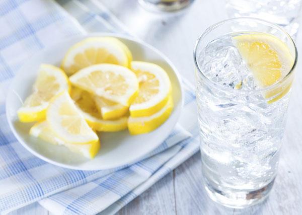 Egy pohár jeges víz, mellette citromkarikák.