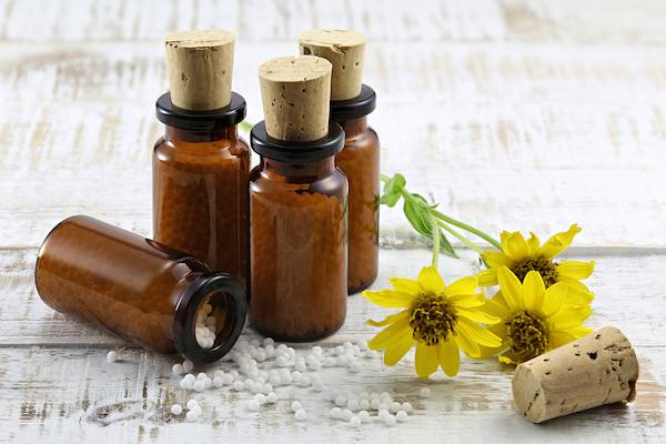 Árnikakivonatot tartalmazó homeopátiás golyók, mellette a gyógynövény.