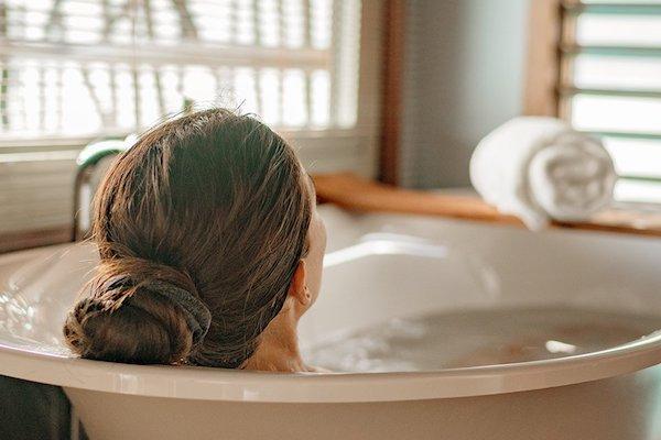 Forró, meleg fürdőt vesz egy hölgy a fürdőszobájában.