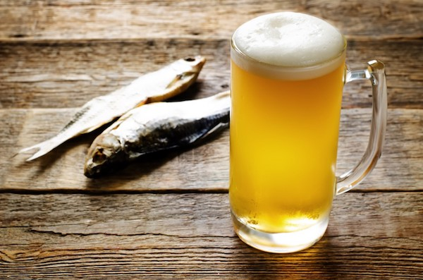 Egy pohár sör az asztalon, mellette két hal.