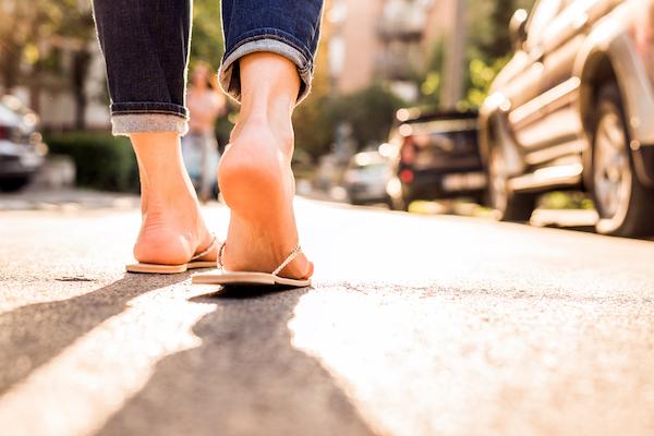Flip-flop papucsban sétál egy nő az utcán.