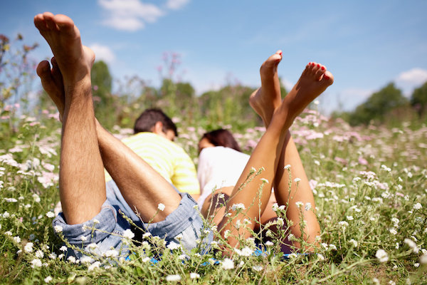Fiatal pár egy virágokkal teli réten feszik a hasán.