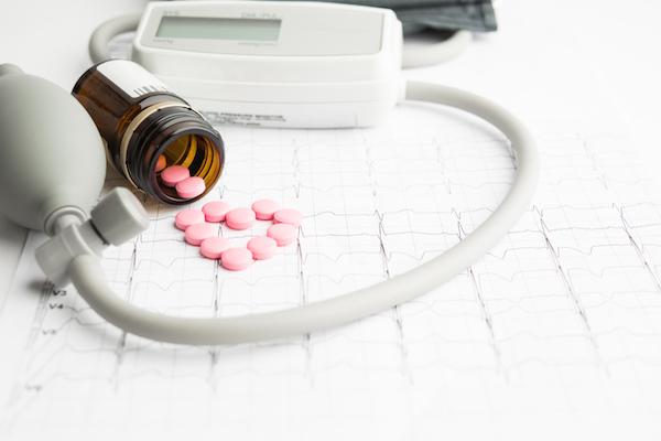 Hagyományos vérnoymásmérő, EKG-s papír, és rózsaszínű, szívet formázó magnéziumtabletták köntve az üvegből.