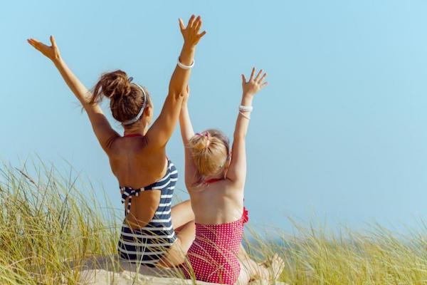 Anya és kislánya kezüket felemelve élvezik a napsütést fürdőruhában.