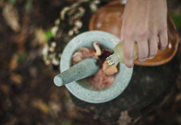 Gyógynövények közé önt illóolajat mozsárba egy kéz.